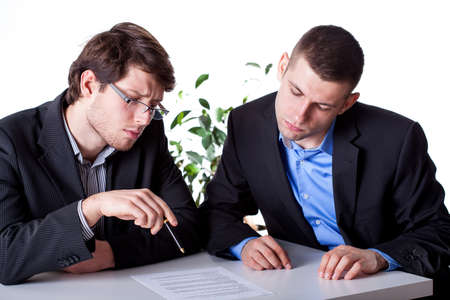 Men in suits reading a contract before signing Stock Photo - 25626899