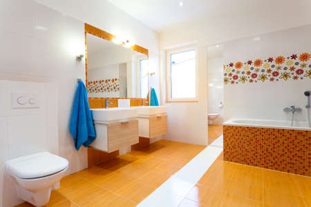 Modern orange bathroom with two sinks and big mirror photo