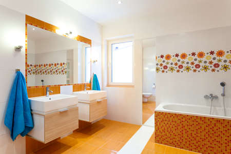 Modern orange bathroom with two sinks for big family  photo