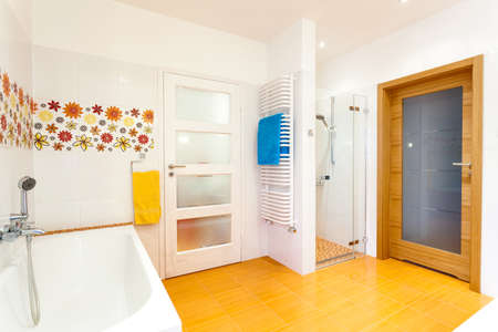 White and orange bathroom with flowers, bath and shower photo