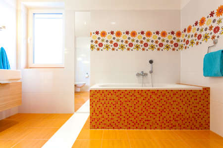 Big orange bath in huge modern bathroom at new house photo