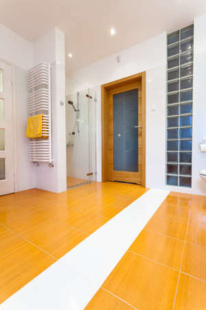 Big orange bathroom with white heater and wooden door photo
