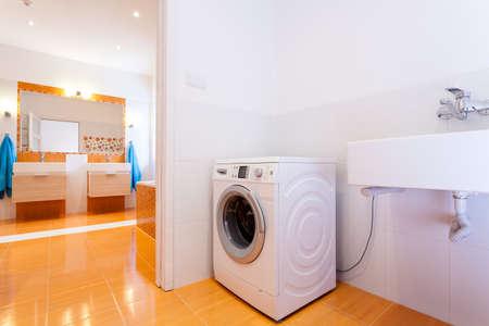 Big comfortable practical bathroom with washing machine at big house Stock Photo - 25626923
