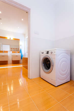 practical: Big practical contemporary bathroom with washing machine in the corner Stock Photo