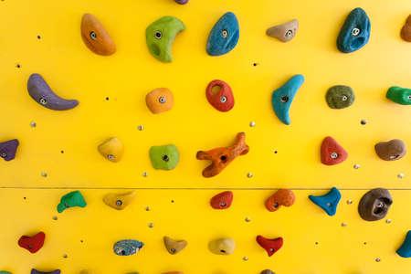 niño trepando: Rocódromo amarillo con piedras de colores