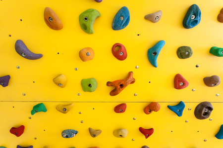 Yellow climbing wall with colorful rocks Stock fotó