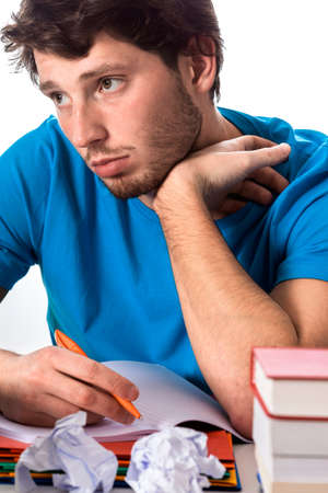 Resigned and tired student trying to write assignment Stock Photo - 25627733