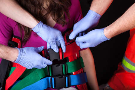 securing: Paramedics securing the casualty with back protecting belts Stock Photo