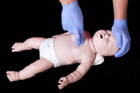 first help: A student practising resuscitation on a plastic baby phantom