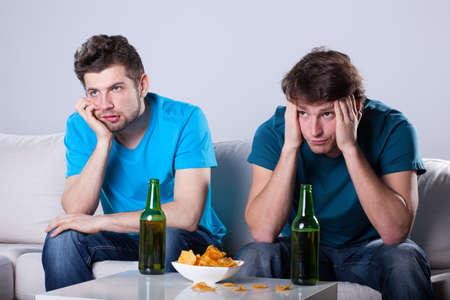 Dva přátelé nudí nad lahví piva a nachos