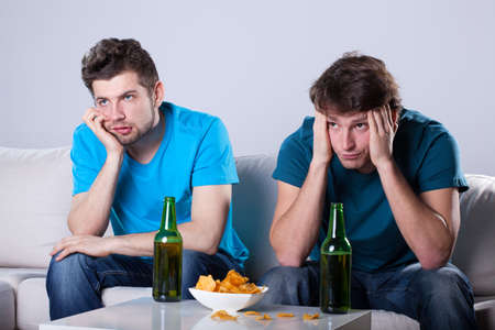 bored man: Two friends bored over bottles of beer and nachos Stock Photo