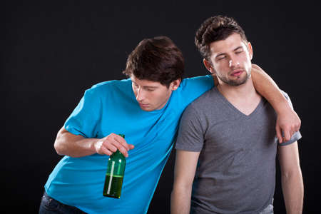 drunk party: Two men friends standing drunk with a bottle of beer Stock Photo