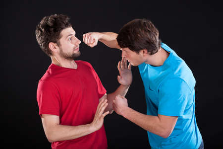 A man threatening the other one with a fist Stock Photo