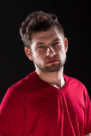 dark brown hair: A portrait of a handsome man with dark brown hair in a red T-shirt
