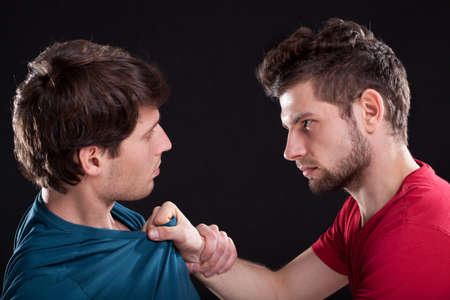 provoking: A closeup of an angry man threatening the other by holding his top