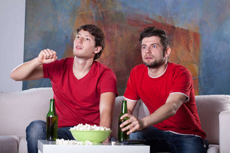 Two men friends watching a movie at home eating popcorn and drinking beer