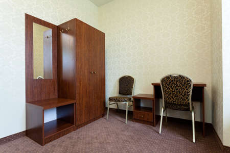 Classic small cozy clean hotel room with brown vintage furniture photo
