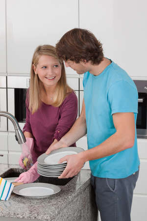 Happy couple working together in modern kitchen photo