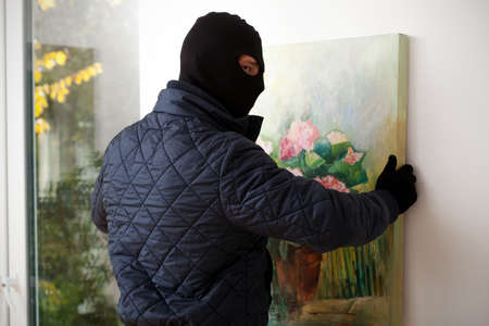 striving: A masked man trying to take a painting off the wall Stock Photo