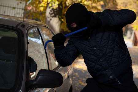 pickpocket: A man breaking in a car through its window