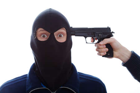 A closeup of a masked terrified burglar with a pistol against his head photo