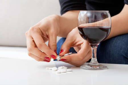 narcotism: Woman taking many antidepressants and drinking red wine