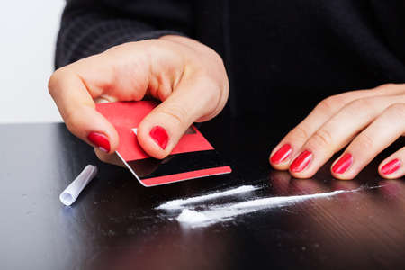 Woman making lines of cocaine with a credit card photo