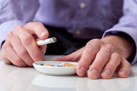 Man Rauchen von Zigaretten und Aschenbecher mit einem Standard-Bild
