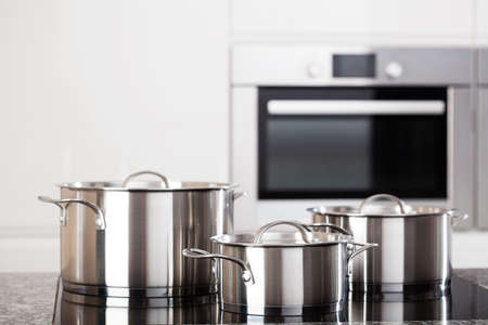 Three new metal pots in the kitchen on induction hob on modern kitchen background Stock Photo