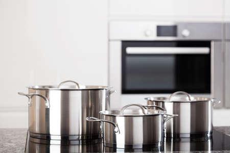 estufa: Tres nuevas ollas de metal en la cocina en placa de inducción en el fondo moderno de la cocina