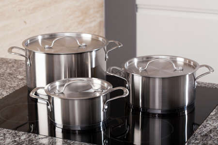 pots and pans: New cookware set on black induction hob in modern kitchen