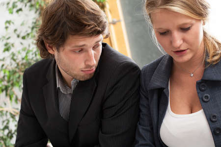 Man looking at decolletage of woman sitting next to him in work
