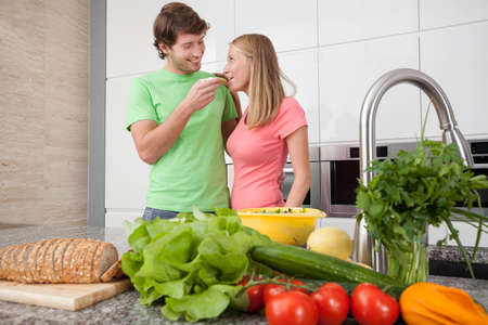 People in love eating lunch together in kitchen photo