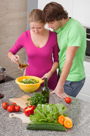Man and woman making a salad with vinaigrette sauce photo