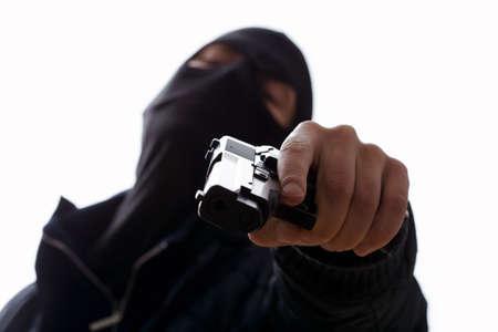 trigger: Un hombre enmascarado apuntando con su arma que sostiene el gatillo Foto de archivo