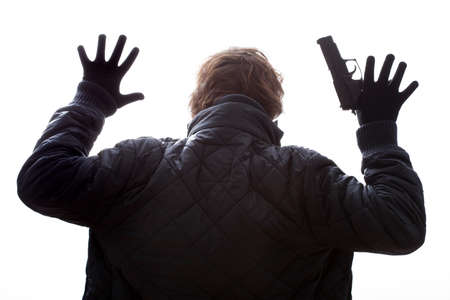 A man with a gun holding his hands up