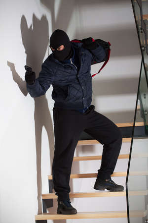 taking a risk: An armed masked robber waiting on the stairs to attack