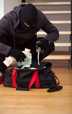 A thief searching a bag with stolen goodies