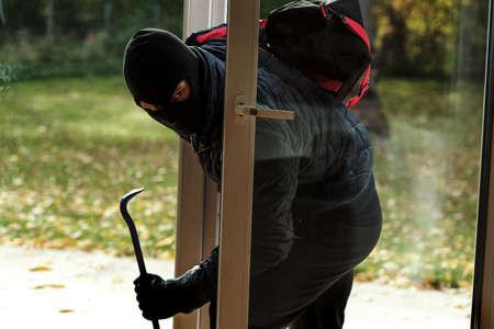ladron: Ladrón de entrar a la casa por la ventana Foto de archivo