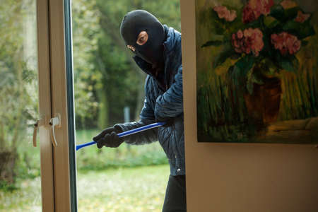 A burglar observing the house from behind the window photo