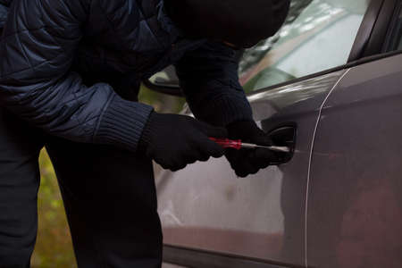 Man wearing a gloves tryng to break into the car photo