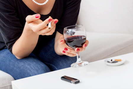 Woman smoking cigarette and drinking red wine