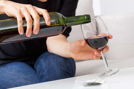 red wine pouring: Woman filling the glass with red wine