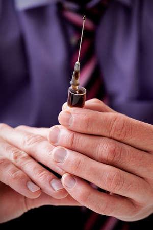 morphine: Businessman addicted to heroin holding a syringe Stock Photo