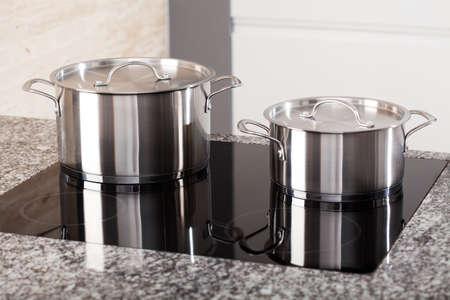 steel pan: Dos nuevas ollas de metal en la cocina de vitrocerámica de inducción Foto de archivo