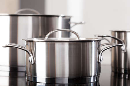 New clean aluminum pots on the kitchen top Stock Photo