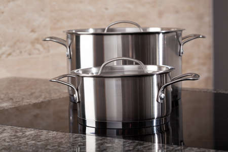 induction: Two new clean aluminum pots on induction hob in the modern kitchen Stock Photo