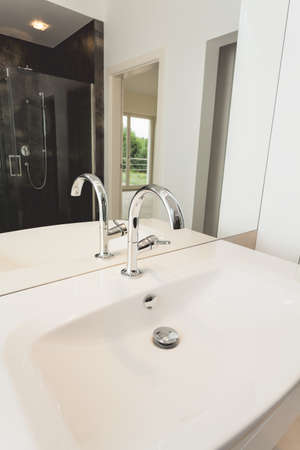 White ceramic bathroom sink and silver tap photo