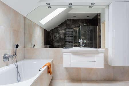 Bright design bathroom furniture and huge mirror photo