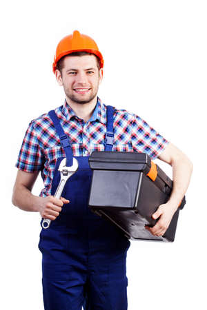 Young happy handyman in blue overalls walking with wrench and toolbox photo